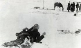 Big Foot Lying in Snow Near Soldiers