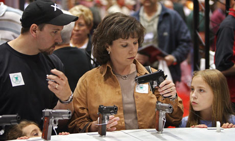A family compare handguns at a National Rifle Association meeting