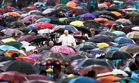 Pope Francis surrounded by Catholics sheltering under umbrellas in St Peter's Square