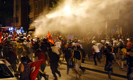 Protesters take cover from water cannon