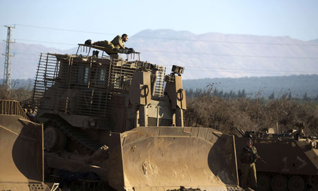 An Israeli soldier rests on his armoured bulldozer