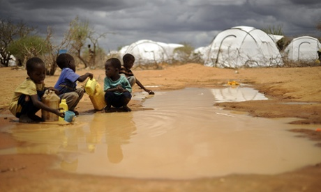 Somali boys fetch water from a puddle that formed after rain at the IFO-2 complex of the sprawling Dadaab refugee complex in Kenya.