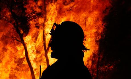 A firefighter gives instructions near a bushfire
