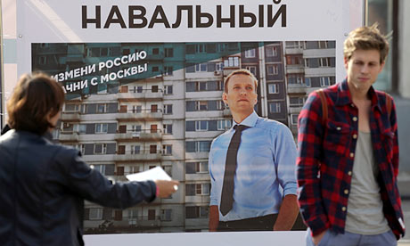 Alexei Navalny supporters hand out flyers in front of a poster during the mayoral campaign in Moscow