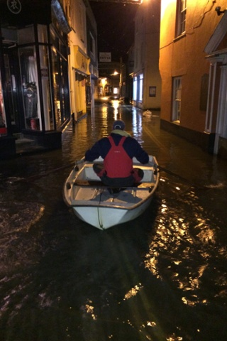 A man rowing down a flooded street in Salcombe, Devon.