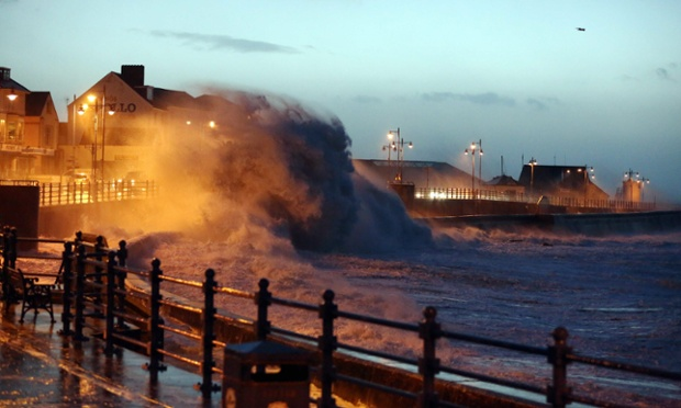 As dawn breaks huge waves crash against the promenade wall in Porthcawl, south Wales.