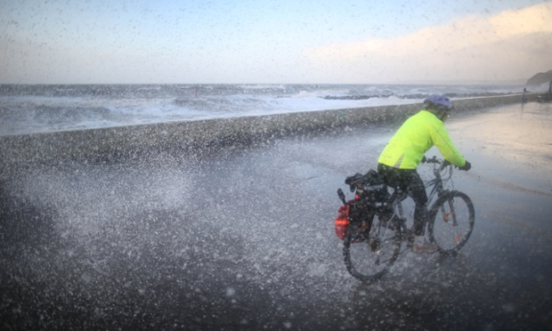 A cyclist gets a soaking on the seafront at West Bay in Dorset.
