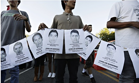 People hold photographs of missing students in Iguala