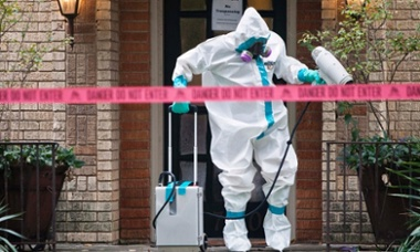 A HazMat worker disinfects the entrance to the residence of a health worker at the Texas Health Presbyterian Hospital who has contracted Ebola in Dallas, Texas.