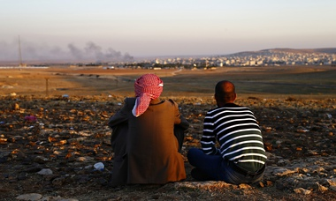 Turkish Kurds watch as smoke from fighting rises over the Syrian border town of Kobani