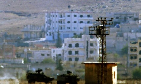 The black Isis banner atop a building in Kobani, taken from over the Turkish-Syrian border. The armo