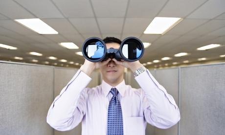 male office worker looking through binoculars