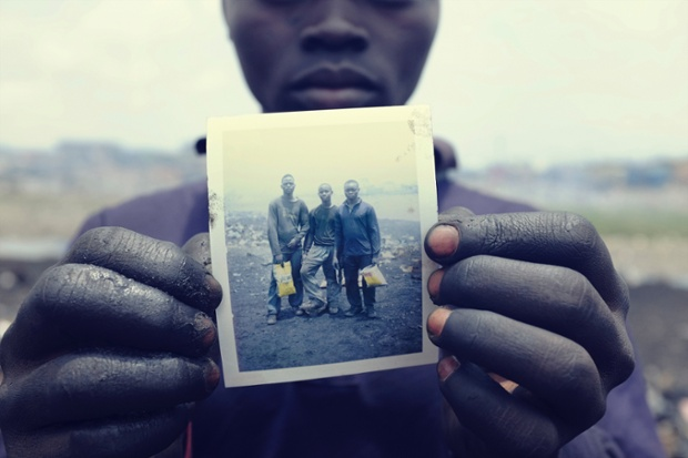 Pieter Adongo, 17, holds a Polaroid of himself and his friends, Desmond Atanga, 17, and Sampson Kwabena, 16