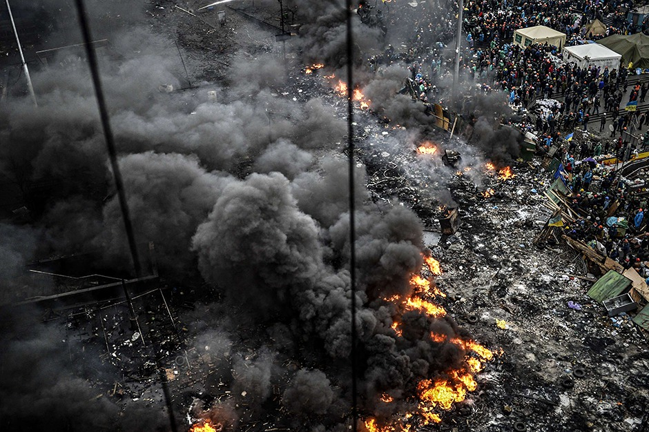 Protesters stand behind burning barricades in Kiev