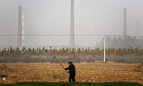 A farmer turning soil to plant crops surrounded by pollution
