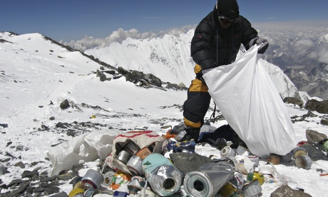 A Nepalese sherpa picks up rubbish left by climbers on Mount Everest