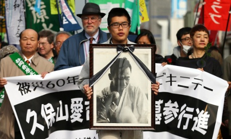 In Yaizu, Japan, a man holds a portrait of Aikichi Kuboyama at a march to mark the Bikini Atoll anniversary.