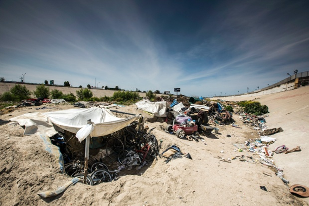 Rubbish surrounds the area, deposited by sewage that runs through the nearby Tijuana River channel. The fence separating the United States and Mexico sits yards away from holes in the ground with shallow inter-connecting tunnels and makeshift tents where people live.