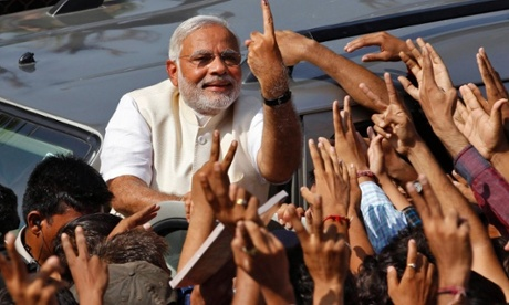 Hindu nationalist Narendra Modi, the prime ministerial candidate for India's main opposition Bharatiya Janata Party (BJP), shows his ink-marked finger to his supporters after casting his vote at a polling station during the seventh phase of India's general election in the western Indian city of Ahmedabad.
