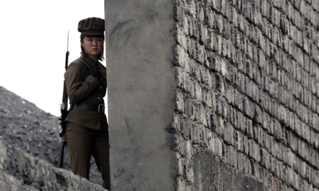 A North Korean soldier patrols the bank of the Yalu River which separates the North Korean town of Sinuiju from the Chinese border town of Dandong, on 26 April 2014.
