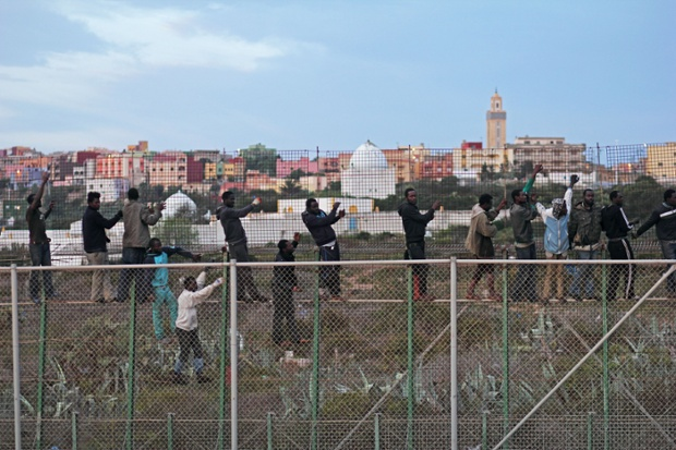 Migrants climb a border fence in March after a dawn assault on the border fence.