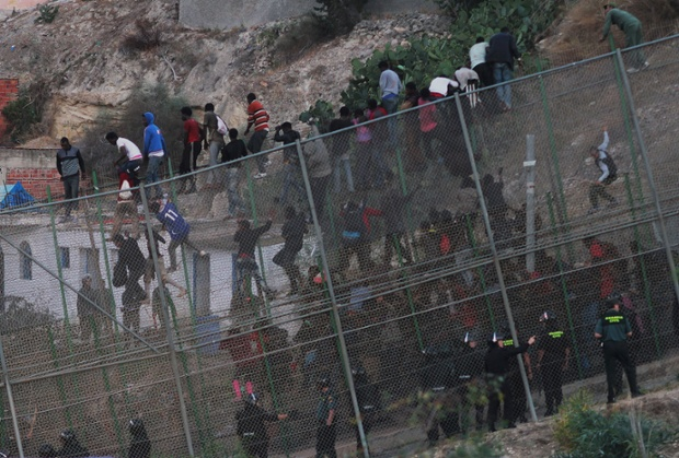 Would-be immigrants try to scale the border fence  unsuccessfully with 150 getting stuck on the fence or between the triple fenced border line.