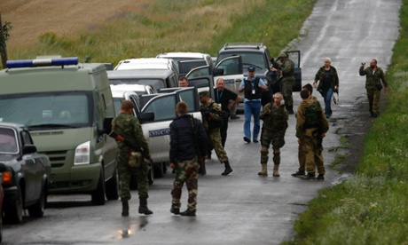 Separatists watch as OSCE monitors arrive at the crash site of Malaysia Airlines flight MH17.
