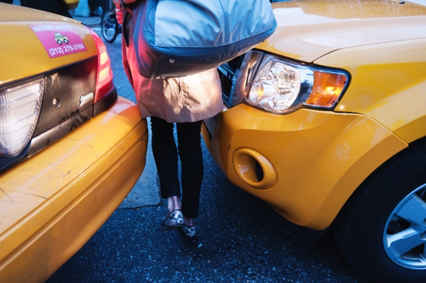 New York City - a Manhattan resident squeezes between two cabs during rush hour.