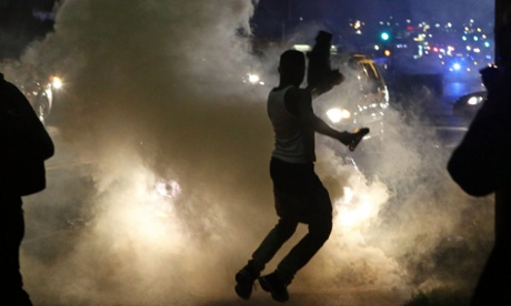 Protesters run when the police shoot tear gas in Ferguson, Missouri.