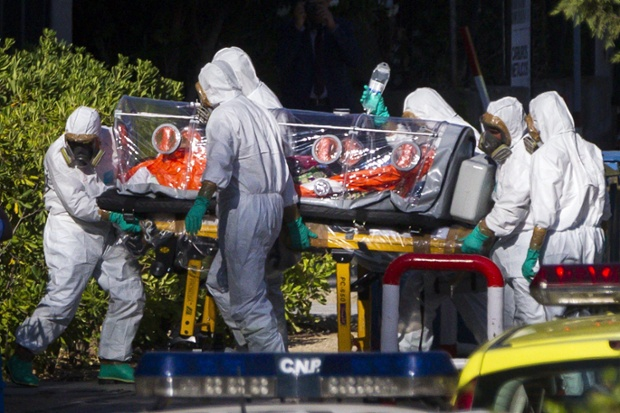 Paramedics wearing protective suits move Miguel Pajares, a Spanish missionary infected with Ebola, on a special isolation stretcher, at Carlos III hospital, in Madrid, Spain