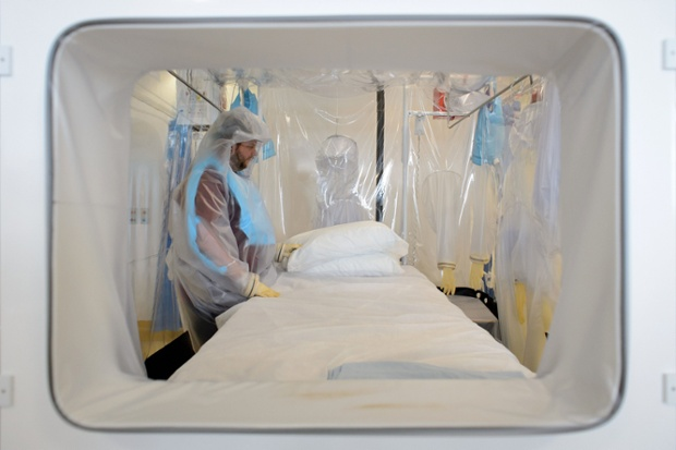 A nurse wears protective clothing to demonstrate the facilities at the Royal Free Hospital. The specialised unit allows a team of doctors and nurses to provide care for anyone with the contagious condition.