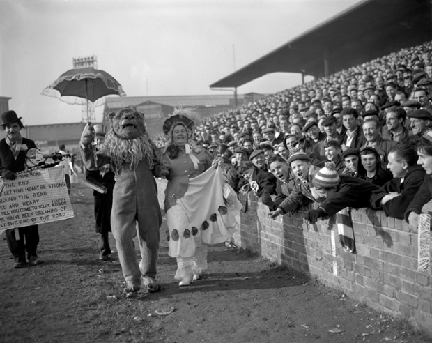 Ada Harwick, as a Gainsborough Lady from Birmingham, and Harry Ansell, as a Millwall Lion, parade along the touch line