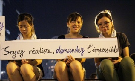 Three students holding a banner that reads 'Soyez r  aliste, demandez l'impossible' (be realistic, demand the impossible), a slogan from the Mai 1968 student movement in France, during pro-democracy demonstrations in Hong Kong.
