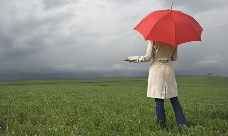 Rear view of woman holding umbrella in field under cloud