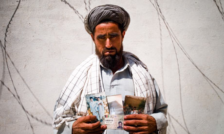 Fazel Muhamad, 48, holding pictures of family members who were killed in the attack. Photograph: Ghaith Abdul-Ahad; The Guardian
