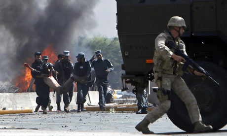 Afghan policemen carry a casualty from blast site