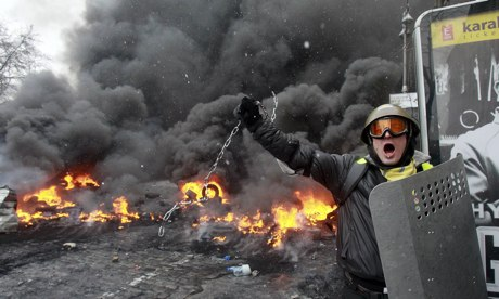 A pro-European protester swings a metal chain during riots in Kiev