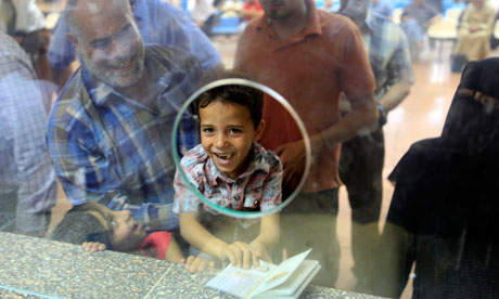 A Palestinian boy holds his father's passport at Egypt's Rafah crossing yesterday. Photograph: Amr Nabil/AP
