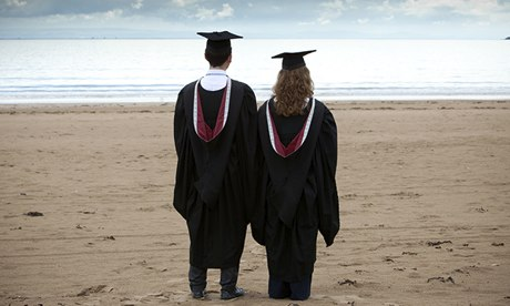 Graduates in gowns gaze at grey sea