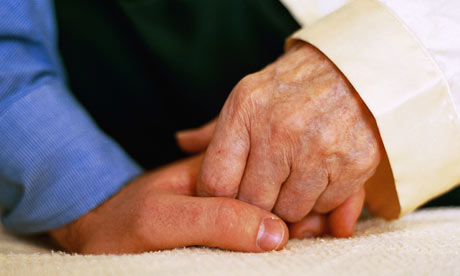 Dementia carer holding hands with patient