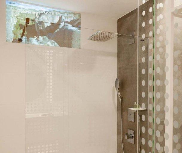 În camerele tehnologice ale NH Collection Eurobuilding te poți uita la televizor în duș.