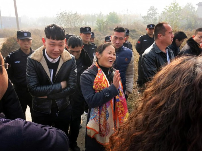 Liu Huizhen, at centre wearing an orange scarf, is surrounded by police and other unidentified men who prevented her from campaigning. Simon Denyer/The Washington Post