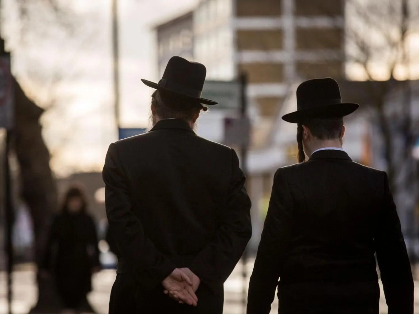 Jewish men walk along the street in Stamford Hill