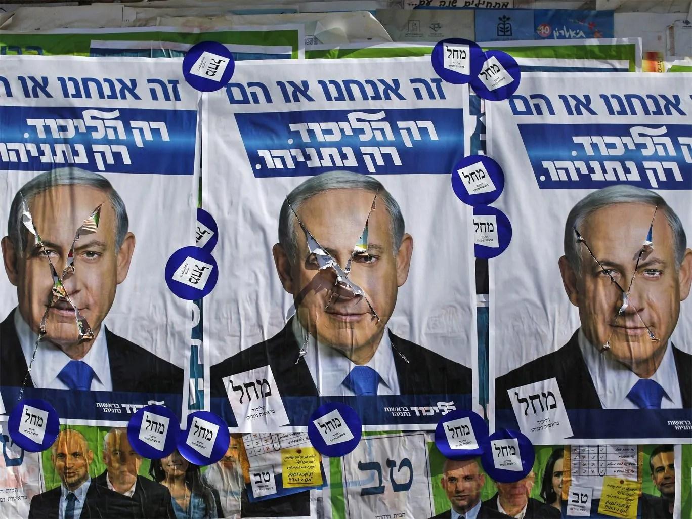 Vandalized posters of Israeli Prime Minister Benjamin Netanyahu near a polling station in the West Bank Jewish settlement of Kiryat Arba, near Hebron