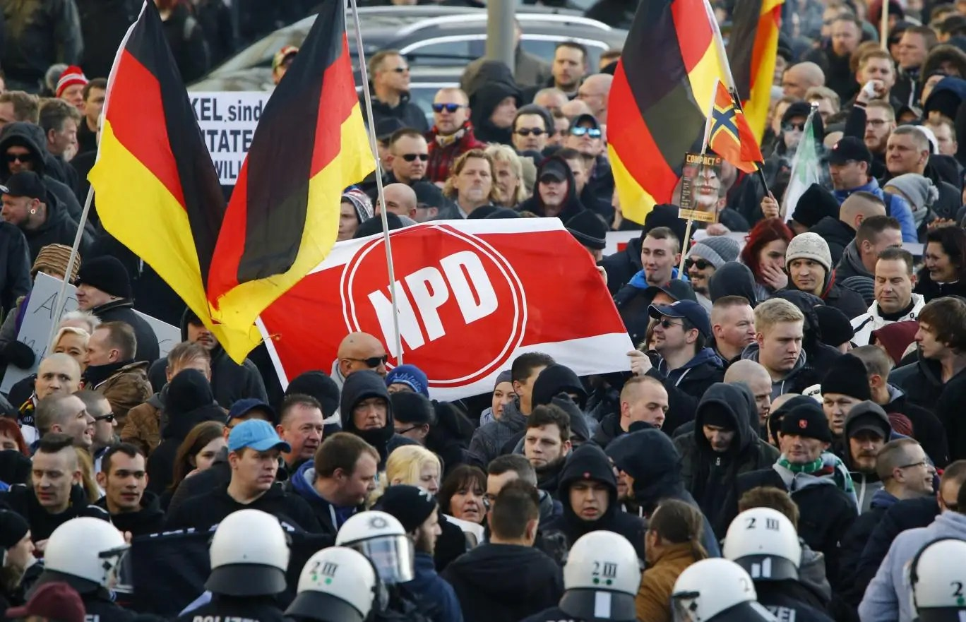 Supporters of anti-immigration right-wing movement PEGIDA hold up a banner with the logo of the far-right National Democratic Party (NPD). Photo: Reuters