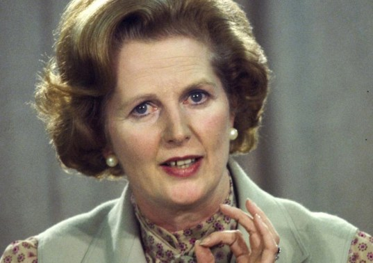 Margaret Thatcher wearing pearl earrings and muted blue waistcoat.