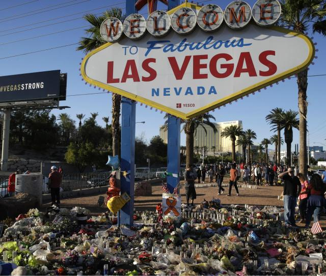 Flowers Candles And Other Items Surround The Famous Las Vegas Sign At A Makeshift Memorial