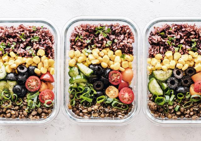 Three glass containers filled with fresh salads including quinoa, corn, cucumber, cherry tomatoes, olives and chopped chives.