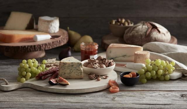 Cutting boards with cheese and bread on table, figs, grapes, and a bowl of olives