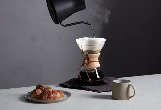 Hot water being poured into a pour-over coffee maker, with a croissant and mug on the side.